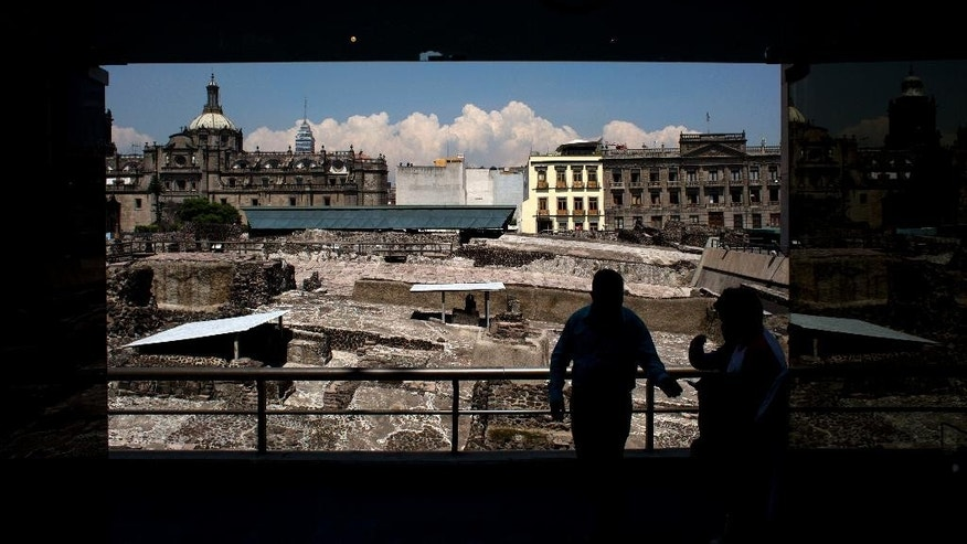 A worker, standing in front of ongoing excavacations at the Templo Mayor archeological site, directs people into the adjoining museum, in central Mexico City, Friday, Aug. 7, 2015. In the pantheon of Mexico's pre-Hispanic gods, most Aztec dieties are depicted as brutal, blood-thirsty gods, only appeased by human sacrifices. But the Templo Mayor museum has put on display for the first time an offering dedicated to Xochipilli, the Aztec god of singing, dancing, and the morning sun. The offering was found in 1978 during excavations of the Red Temple, a small altar adjacent to Templo Mayor. (AP Photo/Rebecca Blackwell)