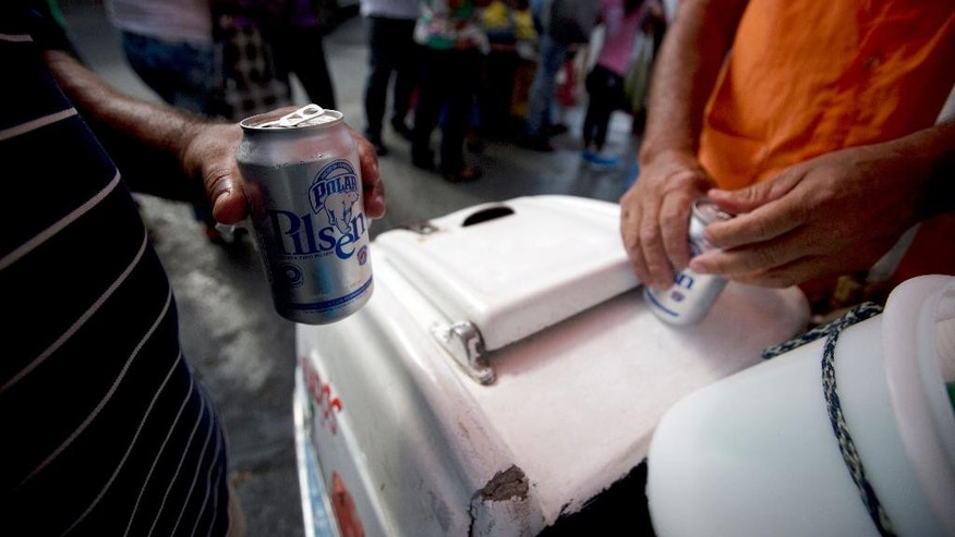 In this Tuesday, July 28, 2015 photo, customers open their cans of Polar beer outside a liquor store in downtown Caracas, Venezuela. Starting Monday Aug. 3, at least two of Polar's six beer plants is closing temporarily for lack of ingredients, affecting 25% of beer production in a country with one of the highest beer consumption rates in the world. Venezuela's President Nicolas Maduro blames food and goods shortages on an economic war waged by opposition aligned companies, while economists point to the country's price controls since 2003. (AP Photo/Fernando Llano)