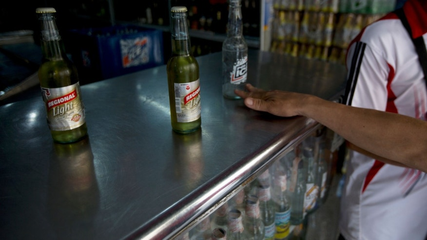 In this Tuesday, July 28, 2015 photo, a customer returns an empty Polar beer bottle and buys two others by another maker after Polar beers sold out at the store in Caracas, Venezuela. Starting Monday, at least two of Polar's six beer plants are closing temporarily for lack of ingredients, affecting 25% of beer production in a country with one of the highest beer consumption rates in the world. Venezuela's President Nicolas Maduro blames food and goods shortages on an economic war waged by opposition aligned companies, while economists point to the country's price controls since 2003. (AP Photo/Fernando Llano)