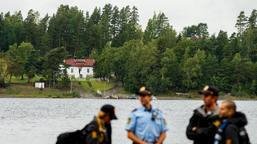 Police stand guard in front of Utoya Island in Norway, Thursday, Aug. 6, 2015. Four years ago a right-wing extremist gunned down 69 people, shattering the tranquility on the idyllic Norwegian island of Utoya after killing eight in a bomb blast at government buildings in the center of the capital Oslo. This week, a flood of newcomers will be arriving on the island as the Labor Party's youth camp opens for the first time since the massacre on July 22, 2011. (Vegard Wivestad Grott/NTB Scanpix via AP)     NORWAY OUT