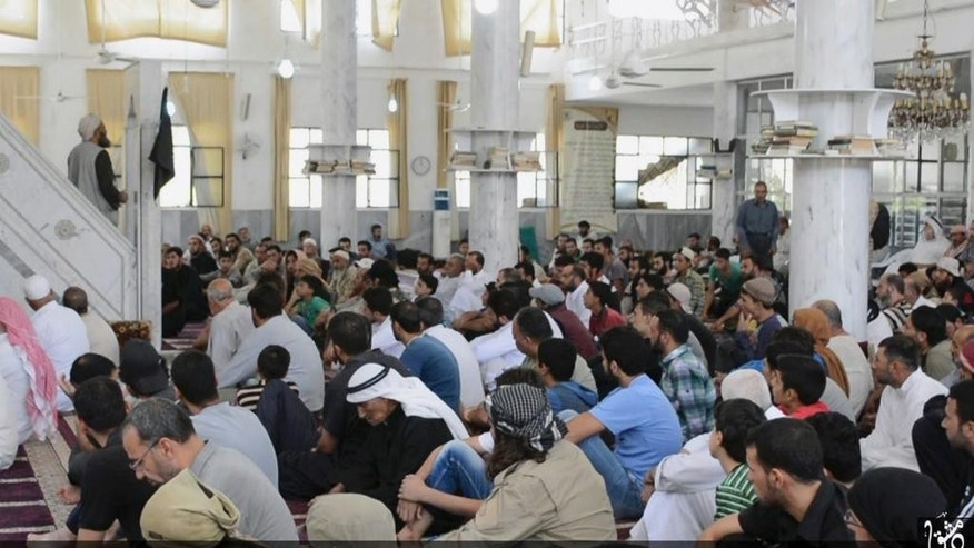 "In this photo provided Friday, Aug. 7, 2015, by the Rased News Network, a Facebook page affiliated with Islamic State militants, Muslim worshipers attend Friday prayers in a mosque in the central Syrian town of Qaryatain. The Arabic on the bottom banner reads, ""Friday prayers after the conquest of Qaryatain."" Activists on Saturday said hundreds of families fled the Christian town of Sadad as Islamic State militants captured Qaryatain on Thursday, which is about 25 kilometers (15 miles) northwest of Sadad. (Rased News Network, a Facebook page affiliated with Islamic State militants via AP)"