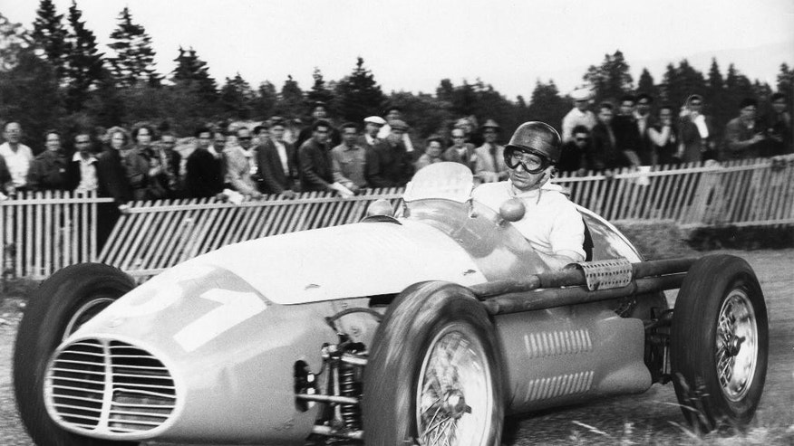 FILE - In this undated file photo, Argentina's Juan Manuel Fangio drives his Maserati race car to win the hill race in the Swiss Jura, Switzerland, at the race track Vue des Alpes. The body of the late Formula 1 star was exhumed in Argentina on Friday, Aug. 7, 2015 by orders of a judge for testing to determine paternity claims brought by two men who believe they are his sons. Fangio, who died in 1995, was never married and did not recognize having any children during his life. Fangio won five world titles between 1951 and 1957. (AP Photo/File)