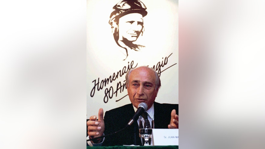 FILE - In this June 21,1991 file photo, Juan Manuel Fangio, a five-time world racing champion, speaks during a celebration commemorating his 80th birthday in Buenos Aires, Argentina. The body of the late Formula 1 star was exhumed in Argentina on Friday, Aug. 7, 2015 by orders of a judge for testing to determine paternity claims brought by two men who believe they are his sons. Fangio, who died in 1995, was never married and did not recognize having any children during his life. Fangio won five world titles between 1951 and 1957. (AP Photo/Eduardo Di Baia, File)