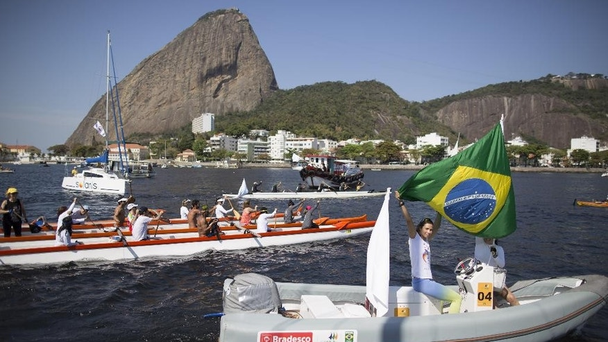 A woman flies Brazil's national flag on her boat during a protest in the Marina da Gloria in Rio de Janeiro, Brazil, Saturday, Aug. 8, 2015. Boats of all sizes paraded across Guanabara Bay to protest contamination in the waters where where sailing events will be held next year during the Olympic Games. Behind is Sugarloaf Mountain. (AP Photo/Leo Correa)