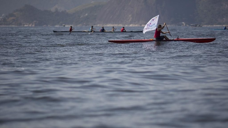 A boater joins a protest against the contamination where where sailing events will be held next year during the Olympic Games, as he rows in the waters of Guanabara bay in Rio de Janeiro, Brazil, Saturday, Aug. 8, 2015. The Living Bay group that organized the protest said that athletes train in the bay under precarious conditions and that the bay should always be in good condition regardless of its use in large events like the Olympics. (AP Photo/Leo Correa)