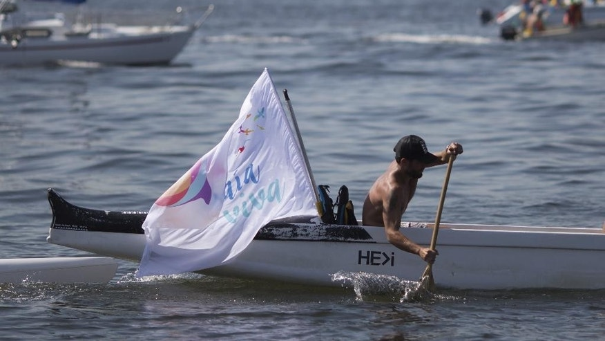 A boater joins a protest against the contamination where where sailing events will be held next year during the Olympic Games, as he rows in the waters of Guanabara bay in Rio de Janeiro, Brazil, Saturday, Aug. 8, 2015. As part of Brazil's Olympic project, authorities pledged more than six years ago to drastically cut the amount of raw human sewage in Guanabara Bay before the 2016 games. But only one of eight promised treatment plants has been built to filter waste from nearby rivers that have become open-air sewage ditches, and the bay's once-crystalline waters remain fetid. (AP Photo/Leo Correa)