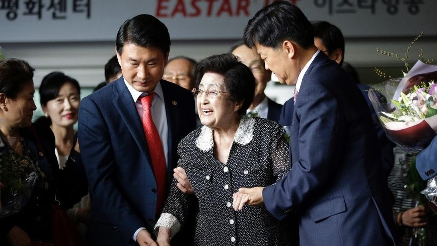 Lee Hee-ho, the widow of former South Korean President and Nobel Peace Prize laureate Kim Dae-jung, is escorted after speaking to the media at Gimpo International Airport in Seoul, South Korea, Saturday, Aug. 8, 2015, after returning from North Korea. Lee returned to Seoul after a four-day visit to North Korea that apparently ended without a meeting with North Korean leader Kim Jong Un. Lee told reporters that she wasn't carrying any official duty on behalf of South Korea during her trip. (AP Photo/Lee Jin-man)