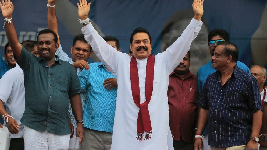 In this July 17, 2015 photo, Sri Lanka's former president and parliamentary candidate Mahinda Rajapaksa, center, waves to supporters during an election campaign rally in Anuradhapura, Sri Lanka. Eight months after a shocking election defeat purportedly ended his absolute control over power and dynastic projects, Sri Lanka's former strongman is on a rebound that could lead to uncertainty and a protracted power struggle in the Indian Ocean island nation. (AP Photo/Eranga Jayawardena)