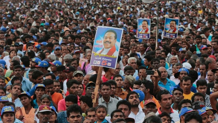 In this July 17, 2015 photo, supporters listen to Sri Lanka's former president and parliamentary candidate Mahinda Rajapaksa during an election campaign rally in Anuradhapura, Sri Lanka. Eight months after a shocking election defeat purportedly ended his absolute control over power and dynastic projects, Sri Lanka's former strongman is on a rebound that could lead to uncertainty and a protracted power struggle in the Indian Ocean island nation. (AP Photo/Eranga Jayawardena)