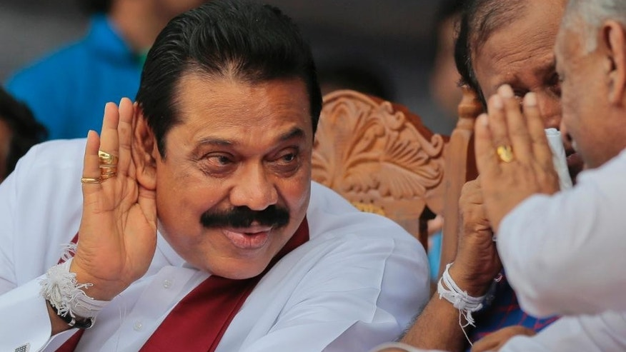 In this July 17, 2015 photo, Sri Lanka's former president and parliamentary candidate Mahinda Rajapaksa listens to a party official during an election campaign rally in Anuradhapura, Sri Lanka. Eight months after a shocking election defeat purportedly ended his absolute control over power and dynastic projects, Sri Lanka's former strongman is on a rebound that could lead to uncertainty and a protracted power struggle in the Indian Ocean island nation. (AP Photo/Eranga Jayawardena)