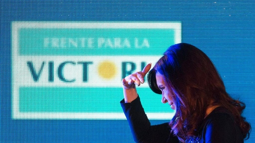"FILE - In this Aug. 12, 2013 file photo, Argentina's President Cristina Fernandez shades her eyes from spotlights next to a logo of her party that reads in Spanish ""Front to the Victory"" after giving a speech regarding the election results in Buenos Aires, Argentina. On Sunday, Aug. 9, 2015, Argentina will hold its open presidential primary election. While Fernandez won't be on the ballot, her influence is all around it. (AP Photo/Victor R. Caivano, File)"