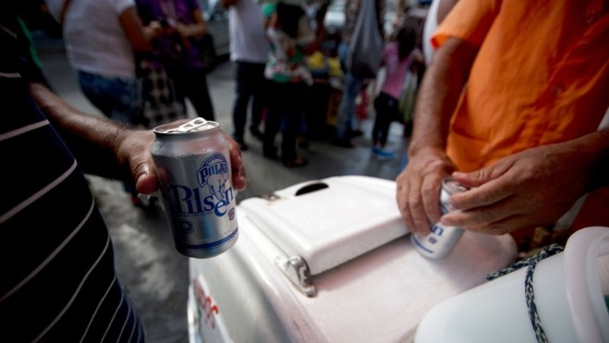In this Tuesday, July 28, 2015 photo, customers open their cans of Polar beer outside a liquor store in downtown Caracas, Venezuela. Starting Monday Aug. 3, at least two of Polar's six beer plants is closing temporarily for lack of ingredients, affecting 25% of beer production in a country with one of the highest beer consumption rates in the world. Venezuela's President Nicolás Maduro blames food and goods shortages on an economic war waged by opposition aligned companies, while economists point to the country's price controls since 2003. (AP Photo/Fernando Llano)