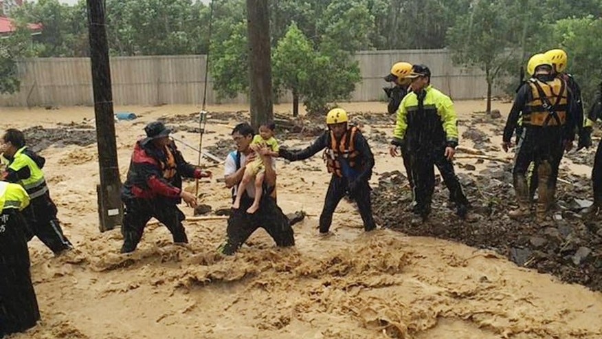In this image released by the New Taipei Fire Department, emergency rescue personnel carry a child through a flash mudslide caused by Typhoon Soudelor in Xindian, New Taipei City, northern Taiwan, Saturday, Aug. 8, 2015. At least four people were killed and four were missing when powerful Typhoon Soudelor slammed into Taiwan, authorities said Saturday. (New Taipei Fire Department via AP)