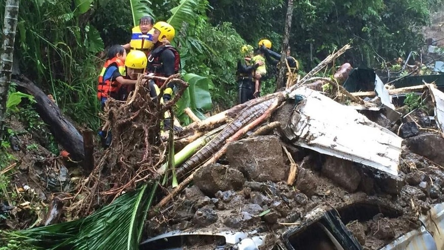 In this image released by the New Taipei Fire Department, emergency rescue personnel carrying children pass crushed cars from a flash mudslide caused by Typhoon Soudelor in Xindian, New Taipei City, northern Taiwan, Saturday, Aug. 8, 2015. At least four people were killed and four were missing when powerful Typhoon Soudelor slammed into Taiwan, authorities said Saturday. (New Taipei Fire Department via AP)