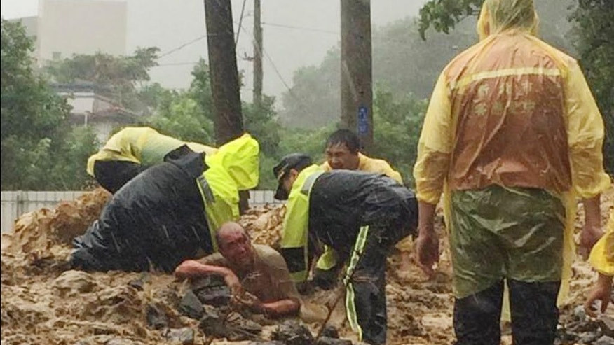 In this image released by the New Taipei Fire Department, emergency rescue personnel dig a man from a flash mudslide caused by Typhoon Soudelor in Xindian, New Taipei City, northern Taiwan, Saturday, Aug. 8, 2015. At least four people were killed and four were missing when powerful Typhoon Soudelor slammed into Taiwan, authorities said Saturday. (New Taipei Fire Department via AP)