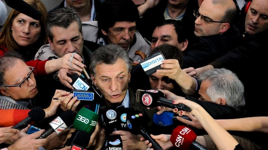 Outgoing mayor of Buenos Aires and presidential candidate Mauricio Macri, center, talks to the press after casting his vote in open primary elections in Buenos Aires, Argentina, Sunday, Aug. 9, 2015. The voters will decide Presidential candidates in their respective parties ahead of the Oct. 25, 2015 general elections. Macri is the top opposition candidate. (AP Photo/Maxi Failla)