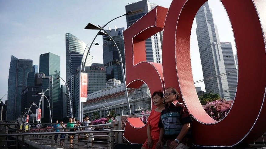 In this Saturday Aug. 8, 2015, photo, a couple sits in front of the number 50 which represents the number of years since Singapore gained independence, in the financial district where celebrations for the nation's 50th year of independence have already started in Singapore. Singapore's 50th anniversary on Sunday commemorates its leap from a poor colonial port to a wealthy metropolis, but leaders are bracing themselves for an uncertain future as resentment continues to grow over political restrictions, an influx of foreigners and high cost of living. (AP Photo/Wong Maye-E)