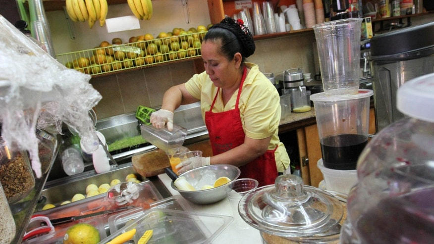 Celina Alvarez, 51, works at Jugueria de regreso al Eden, her shop in the Queens borough of New York, Monday Aug. 3, 2015. As a campaign to raise the minimum wage as high as $15 has rolled to victory in such places as Seattle, Los Angeles and New York, it has bumped up against a harsh reality: Plenty of scofflaw businesses donât pay the legal minimum now and probably wonât pay the new, higher wages either. (AP Photo/Tina Fineberg)