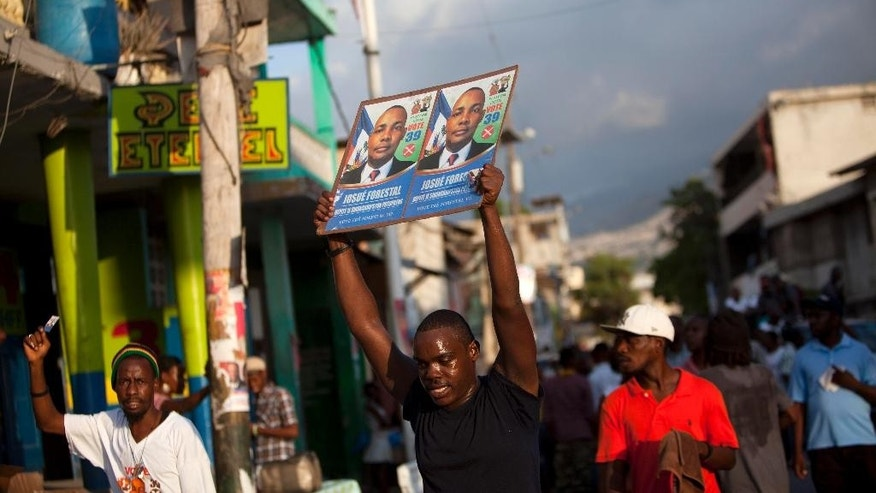 A supporter of parliamentary candidate Josue Forestal holds up Forestal's photo as they campaign for him in Port-au-Prince, Haiti, Thursday, Aug. 6, 2015, ahead of Sunday's parliamentary election. The last parliamentary election was supposed to be held in 2012, but was canceled over disagreements between the reigning party and the opposition. Parliament was dissolved in January of this year, allowing President Michel Martelly to rule under presidential decree. (AP Photo/Dieu Nalio Chery)