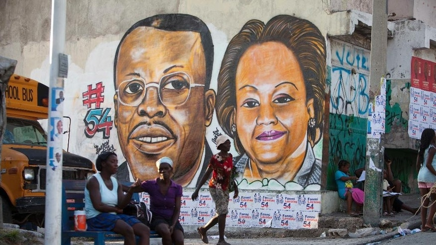 A mural of Maryse Narcisse, right, who leads the Lavalas Family political party, covers a wall along with Haiti's former President Jean Bertrand Aristide in Port-au-Prince, Haiti, Thursday, Aug. 6, 2015. Haiti is expected to hold its first round of presidential elections in October and a final round in December. (AP Photo/Dieu Nalio Chery)