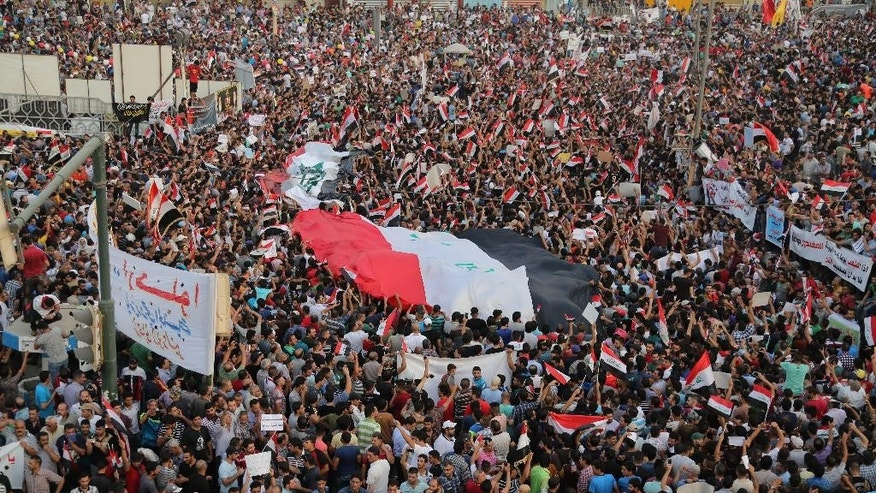 FILE - In this Friday, Aug. 7, 2015, file photo, protesters chant anti-Iraqi government slogans as they carry a large national flag in Tahrir Square in Baghdad, Iraq, Friday, Aug. 7, 2015. Iraq's cabinet approved a wide-ranging reform plan on Sunday that would abolish the three vice presidential posts as well as the office of deputy prime minister in order to slash spending and improve the government's performance in the face of mass protests. (AP Photo/Karim Kadim, File)