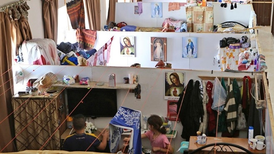 Aug. 8, 2015: Iraqi Christian refugees sit in their rooms in a refugee shelter in a church compound in downtown Amman, Jordan. A year after tens of thousands of Iraqi Christians fled communities overtaken by Islamic State militants, their lives are on hold in exile: They won't go back to Iraq, saying it's not safe for Christians, but as refugees they're barred from working in temporary asylum countries such as Jordan.