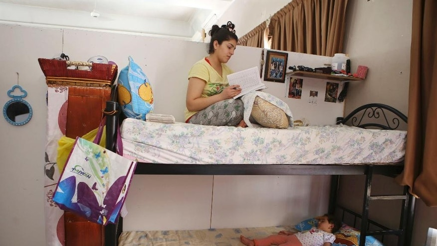 In this Saturday, Aug. 8, 2015 photo, 15-year-old Sarah Atallah, an Iraqi Christian refugee, sits on her bed studying in a refugee shelter in a church compound in downtown Amman, Jordan. A year after tens of thousands of Iraqi Christians fled communities overtaken by Islamic State militants, their lives are on hold in exile: They won't go back to Iraq, saying it's not safe for Christians, but as refugees they're barred from working in temporary asylum countries such as Jordan. Expectations of quick resettlement to the West have been dashed. (AP Photo/Raad Adayleh)