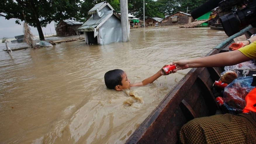 FILE - In this Aug. 7, 2015, file photo, a boy swimming in water receives foods from private donors near half-submerged residences in Nyaung Tone, in the Irrawaddy Delta, southwest of Yangon, Myanmar. Myanmar says the number of people affected by flooding nationwide is approaching 1 million, with waters in the low-lying southwestern region inundating homes and forcing villagers into temporary shelters. Volunteers on small boats were ferrying noodles, rice and clean water door-to-door. Ferocious monsoon rains that began in late June - compounded more recently by Cyclone Komen - have triggered some of the worst flash floods and landslides in recent memory. (AP Photo/Khin Maung Win, File)