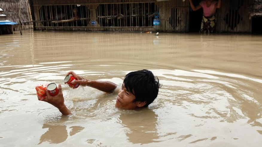 FILE - In this Aug. 7, 2015, file photo, a man in floodwaters receives food aid from private donors as a woman looks from her half-submerged residence in Nyaung Tone, in the Irrawaddy Delta, southwest of Yangon, Myanmar. Myanmar says the number of people affected by flooding nationwide is approaching 1 million, with waters in the low-lying southwestern region inundating homes and forcing villagers into temporary shelters. Volunteers on small boats were ferrying noodles, rice and clean water door-to-door. Ferocious monsoon rains that began in late June - compounded more recently by Cyclone Komen - have triggered some of the worst flash floods and landslides in recent memory. (AP Photo/Khin Maung Win, File)