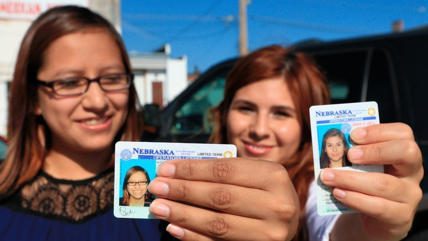 Yajaira Gonzalez, right, a 20-year-old whose parents brought her to Omaha from Mexico shortly before her 9th birthday, and Fatima Flores-Lagunas, 24, a University of Nebraska Omaha junior, pose for a with their drivers licenses in Omaha, Neb., Friday, Aug. 7, 2015. Nebraska has issued 1,300 driverâs licenses to youths who were brought into the country illegally as children since the state became the last in the nation to let them apply. (AP Photo/Nati Harnik)