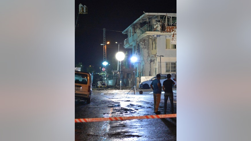 Turkish forensic police officers work at the site of an explosion at a police station in Istanbul's Sultanbeyli neighbourhood, early Monday, Aug. 10, 2015. Turkey's state-run news agency says the attack targeted the police station and wounded five police officers and two civilians. It caused a fire that collapsed part of the building and there was no immediate claim for the attack. (AP Photo/Akin Celiktas)