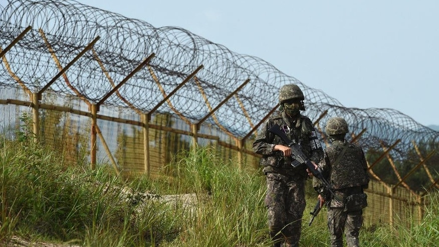 In this Aug. 9, 2015, photo provided by the Defense Ministry, South Korean army soldiers patrol near the scene of a blast inside the demilitarized zone in Paju, South Korea. Vowing to hit back, South Korea said Monday, Aug. 10, 2015, that North Korean soldiers laid the three mines that exploded last week at the border and maimed two South Korean soldiers. (The Defense Ministry via AP)