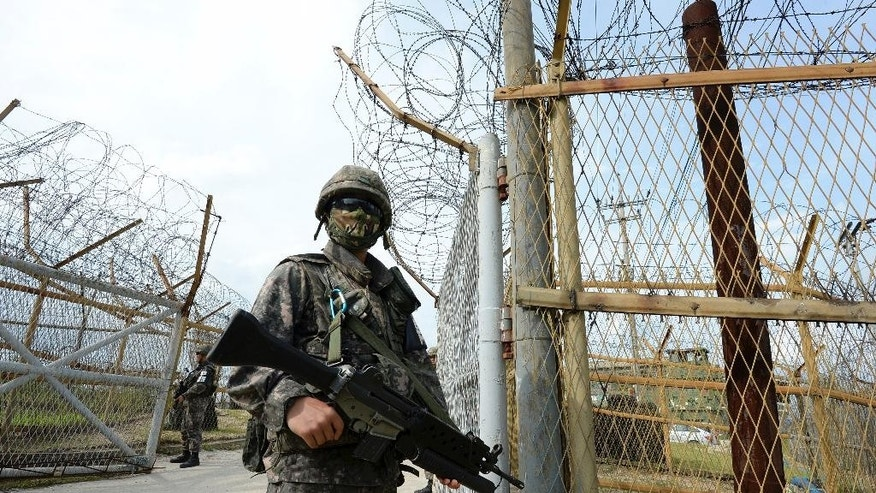 In this Aug. 9, 2015, photo provided by the Defense Ministry, a South Korean army soldier stands guard near the scene of a blast inside the demilitarized zone in Paju, South Korea. Vowing to hit back, South Korea said Monday, Aug. 10, 2015, that North Korean soldiers laid the three mines that exploded last week at the border and maimed two South Korean soldiers. (The Defense Ministry via AP)