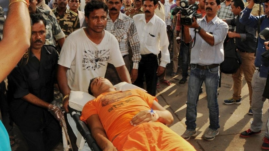 One of the Hindu pilgrims injured in a stampede during a Hindu religious festival at a temple in Deoghar town is brought for treatment at a hospital in Ranchi, Jharkhand state, India, Monday, Aug.10, 2015. Thousands of people tried to force their way into the temple when its gates opened at daybreak, police said. (AP Photo/Sasanka Sen)