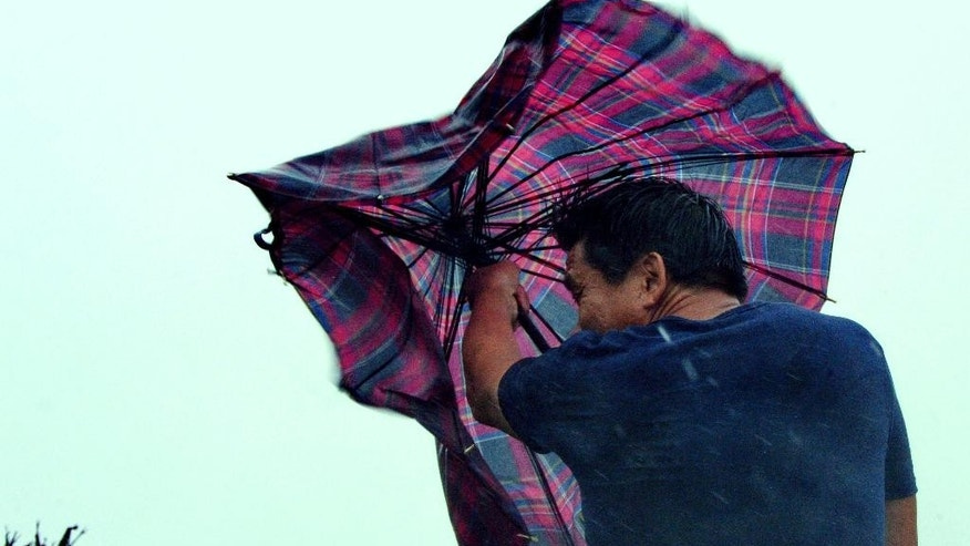 In this Aug. 8, 2015 photo provided by China's Xinhua News Agency, a man walks against gale in Shishi, southeast China's Fujian Province. Typhoon Soudelor hit the city of Putian in Fujian province late Saturday night and weakened into a tropical storm as it moved across the province. The Fujian Civil Affairs Department said that it collapsed 36 houses and damaged 281 others.  (Zhang Guojun/Xinhua News Agency via AP) NO SALES