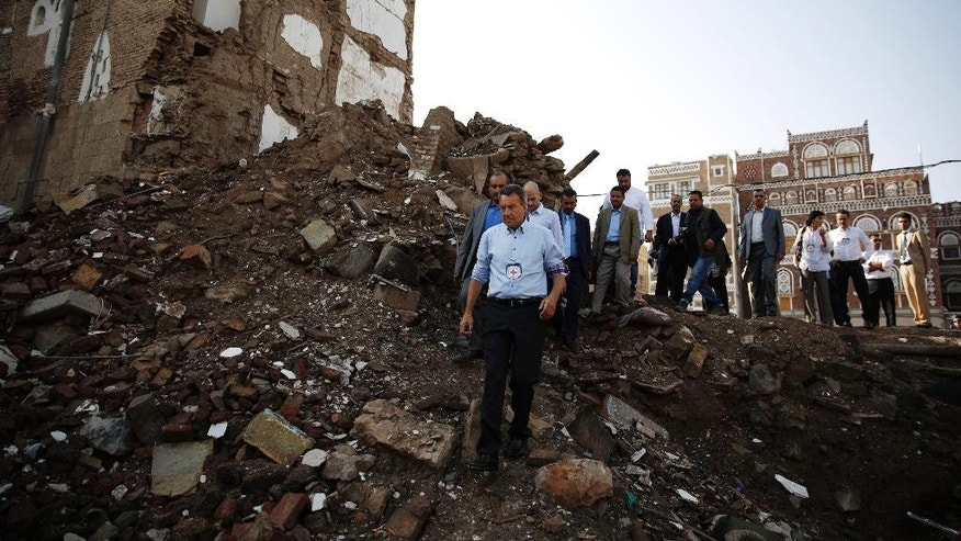 Peter Maurer, the president of the International Committee of the Red Cross, center, walks near houses destroyed by a Saudi-led airstrike during his visit to the old city of Sanaa, Yemen, Sunday, Aug. 9, 2015. (AP Photo/Hani Mohammed)