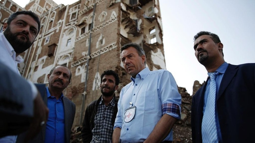 Peter Maurer, the president of the International Committee of the Red Cross, center, stands near houses destroyed by a Saudi-led airstrike during his visit to the old city of Sanaa, Yemen, Sunday, Aug. 9, 2015. (AP Photo/Hani Mohammed)