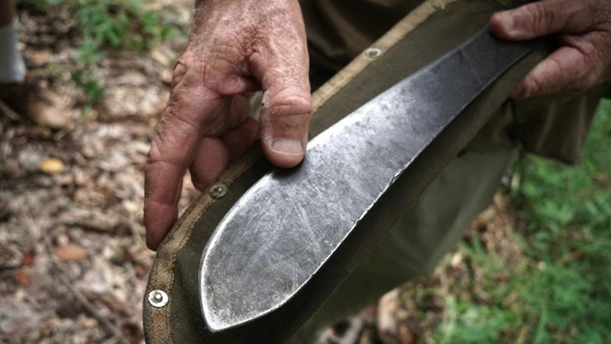 In this June 18, 2015, photo, Rod Beattie shows how his machete has lost metal from years of using it to uncover the path of the Death Railway in Nam Tok, Kanchanaburi province, Thailand. As the 70th anniversary of World War II's end approaches and its veterans dwindle by the day, Beattie, an Australian, still slogs along the 415 kilometer (257 mile) length of Death Railway where more than 100,000 Allied prisoners and Asians were enslaved by Japan's Imperial Army to build the line along the Thailand-Myanmar border. With his own money, he maps its vanishing course, uncovers POW relics and with his vast database helps brings closure to relatives of those who perished and survivors who went to their graves never having shared their traumas. (AP Photo/Charles Dharapak)