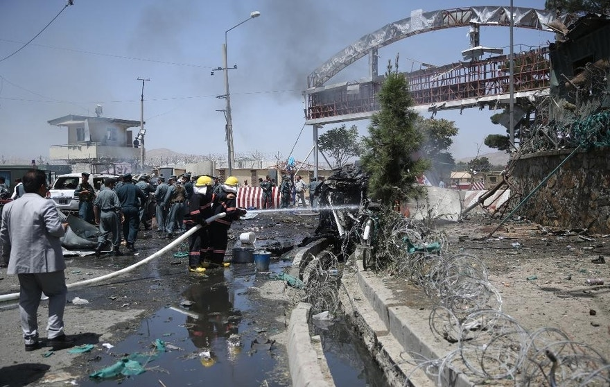 Afghan fire fighters extinguish vehicles on fire after an attack at the main gate of International Hamed Karzai Airport in Kabul, Afghanistan, Monday, Aug. 10, 2015. An explosion on Monday at a busy roundabout near the entrance to Kabul's international airport that wounded at least seven people appears to have been caused by a suicide car bomb, officials said. (AP Photo/Massoud Hossaini)