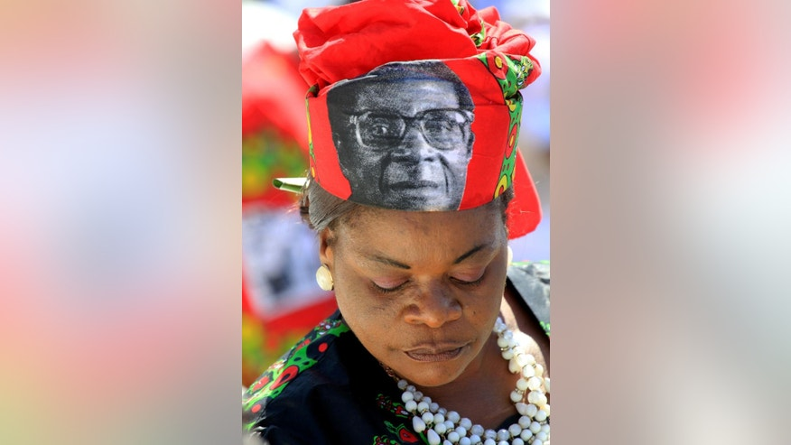 A woman wearing headwear showing an image of Zimbabwean President Robert Mugabe attends a ceremony to honour thousands of fighters who died in a 1970s Bush war against colonialism in Harare, Monday Aug. 10, 2015. Mugabe, in his first public comments about the popular lion named Cecil, says his compatriots failed in their responsibility to protect the lion that was killed by an American in an allegedly illegal hunt. (AP Photo/Tsvangirayi Mukwazhi)