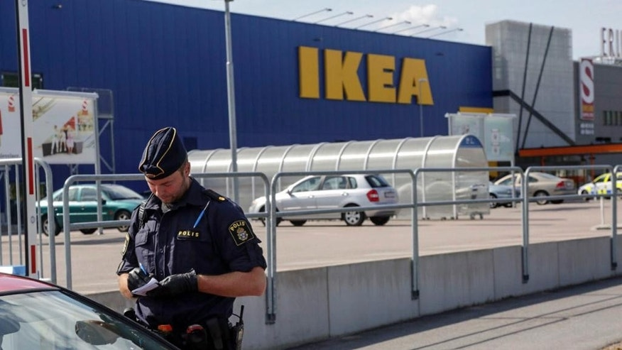 Aug. 10, 2015: A police officer talks to customers outside the Ikea store in Vasteras, Sweden.