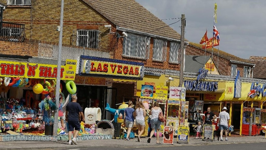 A view of holiday amusements in Leysdown On Sea in Kent, England, Tuesday, Aug. 4, 2015. This summer, Britain's headlines have been dominated by one story _ thousands of migrants massing in France, aiming to get to England through the Channel Tunnel. They are not flocking to places like Leysdown-on-Sea, about 50 miles (80 kilometers) from the migrant camps at Calais. In fact, there are hardly any migrants to be seen in this faded seaside town, with its pubs, chip shops and amusement arcades that seem scarcely to have changed since the 1970s. It's a poor corner of England where good jobs are hard to come by even for the locals. (AP Photo/Kirsty Wigglesworth)