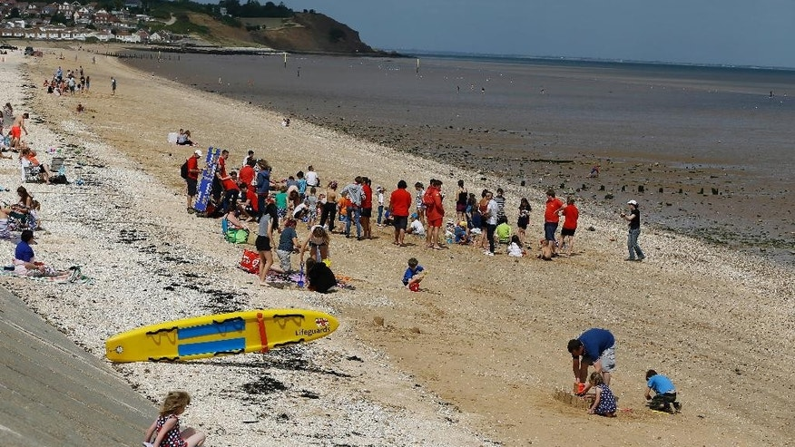 Holiday makers enjoy the beach in Leysdown On Sea in Kent, England, Tuesday, Aug. 4, 2015. This summer, Britain's headlines have been dominated by one story _ thousands of migrants massing in France, aiming to get to England through the Channel Tunnel. They are not flocking to places like Leysdown-on-Sea, about 50 miles (80 kilometers) from the migrant camps at Calais. In fact, there are hardly any migrants to be seen in this faded seaside town, with its pubs, chip shops and amusement arcades that seem scarcely to have changed since the 1970s. (AP Photo/Kirsty Wigglesworth)