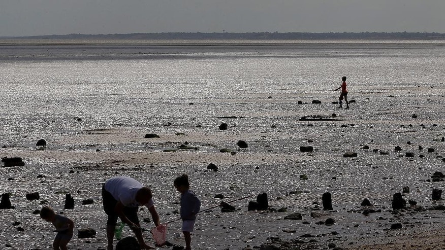 Holiday makers enjoy the beach in Leysdown On Sea in Kent, England, Tuesday, Aug. 4, 2015. This summer, Britain's headlines have been dominated by one story _ thousands of migrants massing in France, aiming to get to England through the Channel Tunnel. They are not flocking to places like Leysdown-on-Sea, about 50 miles (80 kilometers) from the migrant camps at Calais. In fact, there are hardly any migrants to be seen in this faded seaside town, with its pubs, chip shops and amusement arcades that seem scarcely to have changed since the 1970s. It's a poor corner of England where good jobs are hard to come by even for the locals. (AP Photo/Kirsty Wigglesworth)