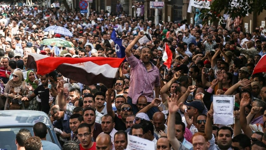 Tax and custom workers protest against a new law seeking to reform the country's mammoth civil service, calling it unfair and unconstitutional, in Cairo, Monday, Aug. 10, 2015. About 2,000 tax and customs workers protested Monday in Cairo, urging President Abdel-Fattah el-Sissi to scrap the law and fire his finance and planning ministers. It was one of the largest anti-government rallies amid a crackdown on dissent.  (AP Photo/Mohamed Elraai)