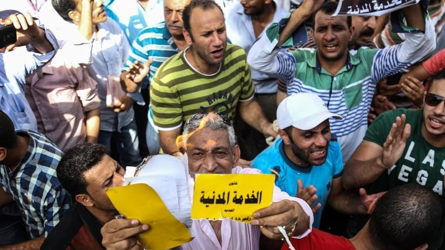 A protestor tears and burns a card, reading in Arabic: The Civil Service Law, in Cairo, Monday, Aug. 10, 2015. Egyptian tax collectors have rallied against a new law seeking to reform the country's mammoth civil service, calling it unfair and unconstitutional. (AP Photo/Mohamed Elraai)