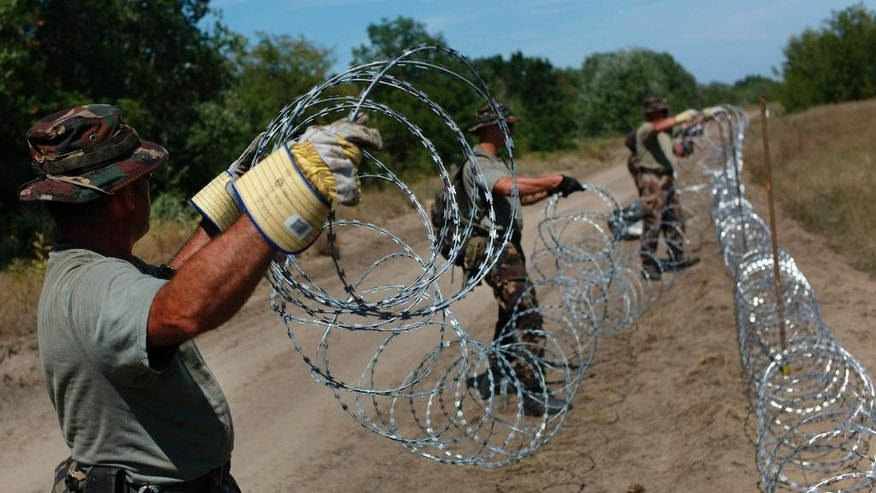 Hungarian soldiers  build a fence on the Hungarian - Serbian border near Asotthalom, Hungary on Monday Aug. 10, 2015, as the flow of migrants continues to hit Hungary's southern borders. More than 100,000 migrants have reached Hungary on routes across the Balkans so far in 2015. Recently, some 80 percent of them are from war zones like Syria, Iraq and Afghanistan. (AP Photo/Bela Szandelszky)