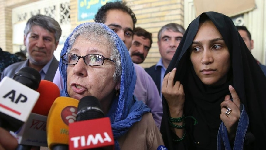 Mary Rezaian, mother of detained Washington Post correspondent Jason Rezaian, speaks with media as Jason's wife Yeganeh adjusts her scarf, right, while leaving a Revolutionary Court building in Tehran, Iran, Monday, Aug. 10, 2015. The final hearing of Rezaian detained in Iran more than a year ago and charged with espionage ended on Monday, Aug. 10, 2015 with a verdict expected in the coming days in a trial that has been condemned by the newspaper and press freedom groups. (AP Photo/Vahid Salemi)