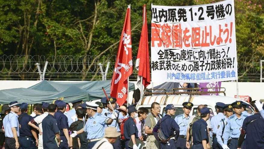 "Police officers stand guard as protesters stage a rally at the gate of the Sendai Nuclear Power Station in Satsumasendai, Kagoshima prefecture, southern Japan, Tuesday, Aug. 11, 2015. The power plant operator Kyushu Electric Power Co. has restarted a reactor, the first to begin operating under new safety requirements following the Fukushima disaster. The banner reads: ""Stop the resumption of operation"". (Hiroko Harima/Kyodo News via AP) JAPAN OUT, MANDATORY CREDIT"