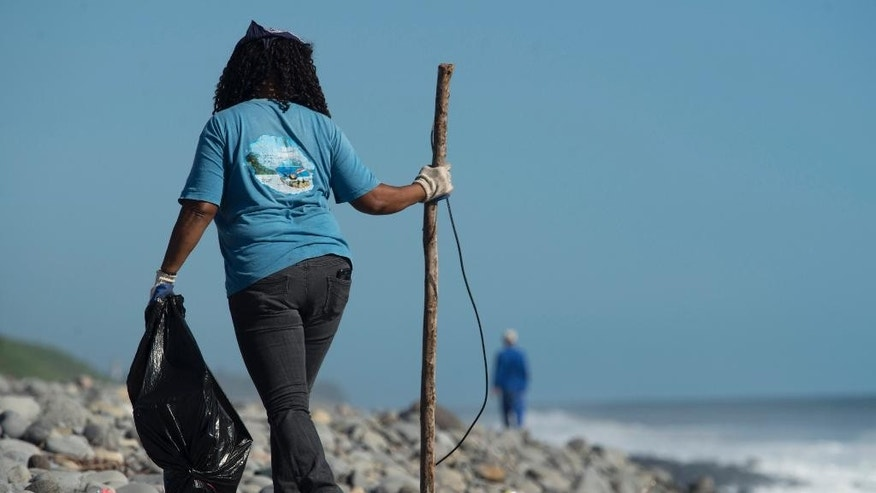 A Municipal worker searches Reunion Island beaches where expected debris of the missing Malaysia Airlines Flight 370 could be washed up onto the shore near Saint-Andre, Reunion island. The Malaysian plane disappeared on March 8, 2014, while flying from Kuala Lumpur, Malaysia, to Beijing, China. (AP Photo/Fabrice Wislez)